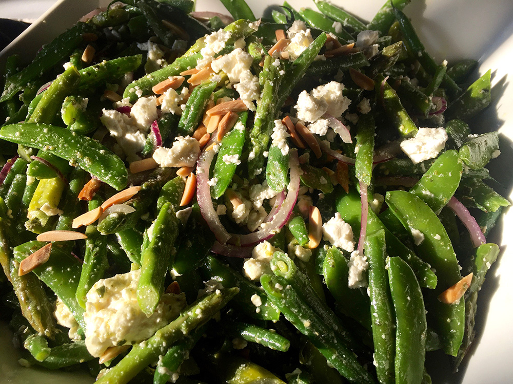 Sugar snap pea salad with red onions, feta cheese and toasted and slivered almonds